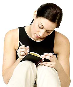 GERD diet: woman writing in a book. Keeping a journal.
